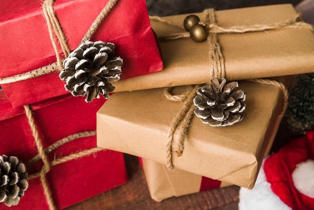 Scatole regalo decorate vicino a strappi e cappello natalizio