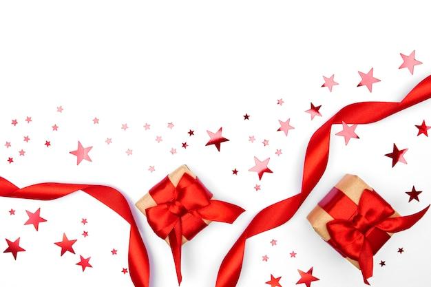 Scatole regalo di carta artigianale con fiocco in nastro rosso, coriandoli stella isolato