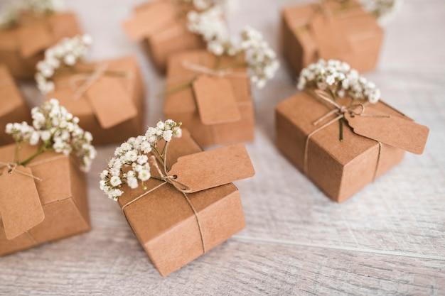 Scatole regalo di cartone con tag e fiori baby's-breath sulla scrivania in legno
