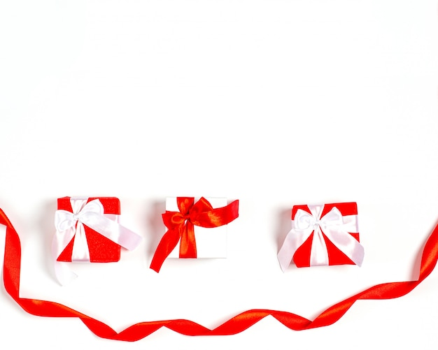 Scatole regalo di compleanno con nastri rossi e un nastro largo rosso nella parte inferiore.