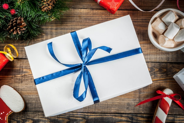 Scatole regalo di natale decorate, con una tazza di cioccolata calda, pan di zenzero e rami di alberi di natale