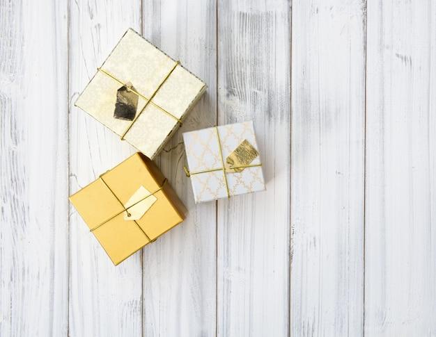 Scatole regalo di natale dorato impostato su sfondo di legno bianco, piatto laici