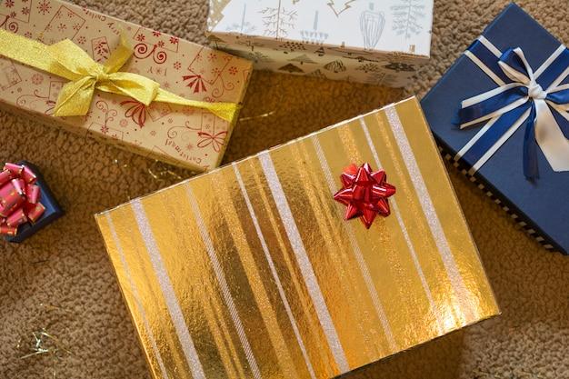 Scatole regalo di natale oro e blu con pompon rosso.
