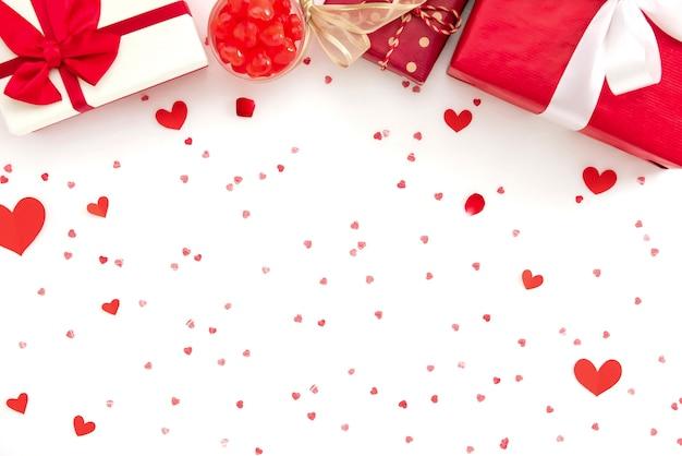 Scatole regalo e caramelle su texture di carta cuore rosso