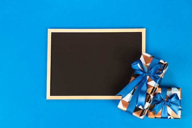 Scatole regalo e lavagna su sfondo blu con spazio di copia.