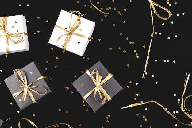 Scatole regalo in bianco e nero con nastro d'oro. disteso. copia spazio