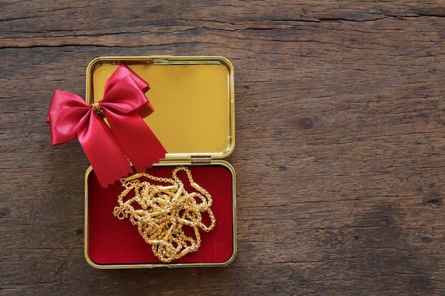 Scatole regalo in oro con collana in oro e nastro su fondo di legno marrone