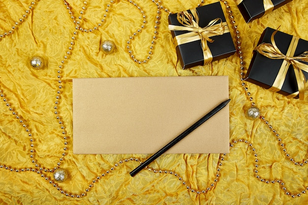 Scatole regalo nero con nastro oro e foglio di carta bianco
