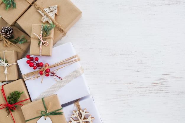 Scatole regalo presenti fatte a mano di sfondo di natale con etichetta per le vacanze di natale e capodanno. layout piatto creativo e composizione vista dall'alto con bordo e copia spazio design.