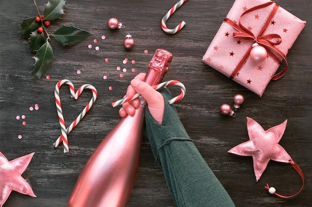 Scatole regalo rosa, bastoncini di zucchero a strisce a forma di cuore, bigiotteria e stelle decorative, piatto creativo con bottiglia di champagne di rose in mano femminile.
