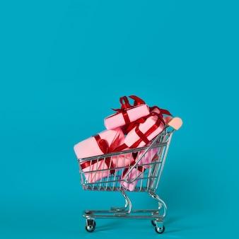 Scatole regalo rosa nel carrello. saldi delle vacanze, concetto.