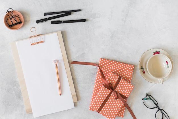 Scatole regalo rosse, occhiali, appunti e penne