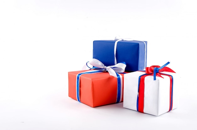 Scatole regalo rosso, blu e bianco con nastri su uno sfondo bianco