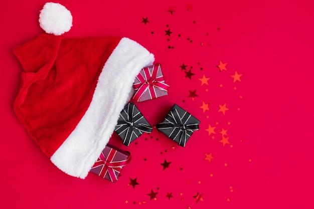Scatole regalo rosso, nero piccolo regalo in cappello di babbo natale su sfondo rosso intenso