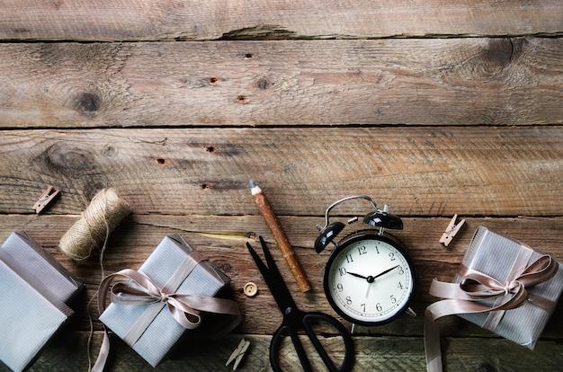 Scatole regalo, sveglia nera, penna, forbici su legno. preparazione per il compleanno, natale, capodanno.