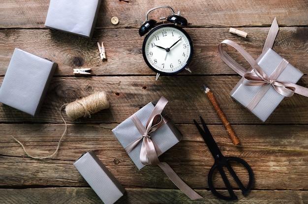 Scatole regalo, sveglia nera, penna, forbici su legno.