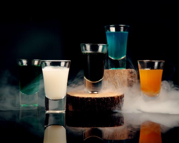 Scatti in bicchieri di diversi colori sullo sfondo del fumo