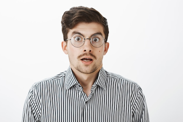 Scatto alla vita di un ragazzo barbuto e scioccato sorpreso con i baffi in occhiali trasparenti rotondi, mascella cadente, che dice wow e fissa, vedendo prezzi scioccanti e fantastici sul muro grigio