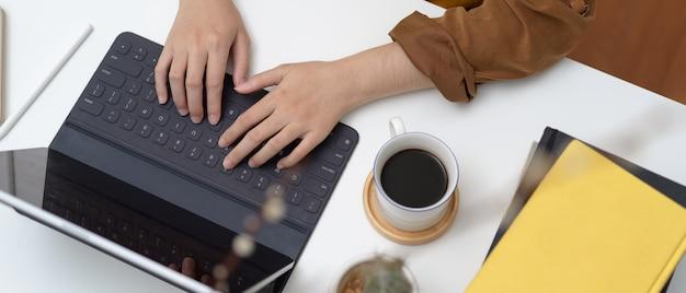 Scatto dall'alto di studente che digita sulla tastiera del tablet sul tavolo da lavoro con una tazza di caffè