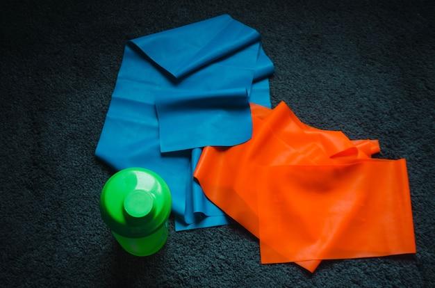 Scatto dall'alto di una boccetta d'acqua vicino a gomme blu e rosse sul pavimento