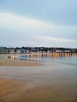 Scatto verticale di uno scenario serale affascinante di luci della città che si riflettono nell'oceano