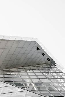 Scatto verticale in scala di grigi di una struttura geometrica catturata da un angolo basso