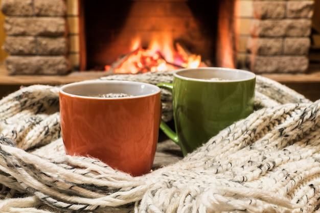 Scena accogliente vicino al camino con tazze di tè caldo e calda sciarpa accogliente.