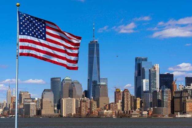 Scena della bandiera dell'america sopra il lato del fiume di paesaggio urbano di new york quale posizione è più bassa manhattan