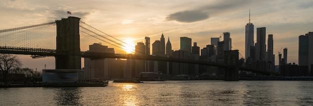 Scena della bandiera e della copertura di new york cityscape con il ponte di brooklyn sopra il fiume orientale al tramonto