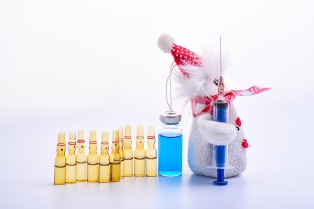 Scena di natale e medicina un pupazzo di neve che tiene una siringa come una pistola e guida un esercito di fiale mediche