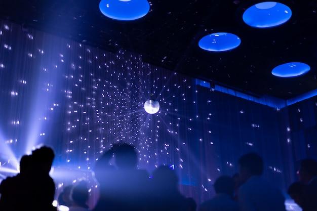 Scena di notte concetto offuscata nella festa di concerto con pubblico silhoette.