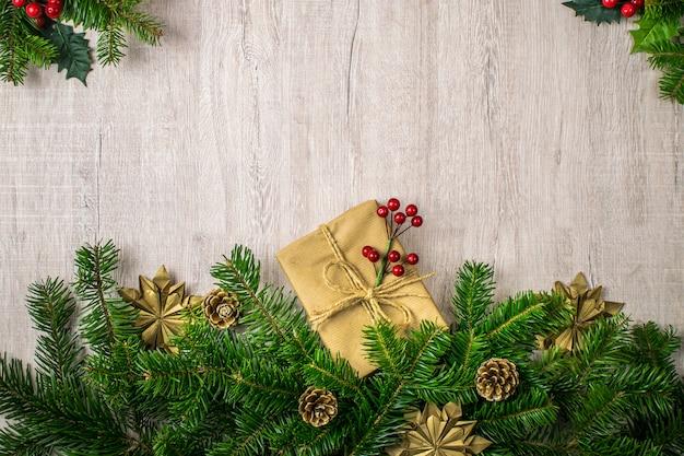 Scena di vacanze di natale con regali di natale, pigne, rami di abete, vischio, fiocchi di neve su uno sfondo di legno piacevole