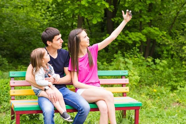 Scena estiva di giovane famiglia felice che cattura selfie con il suo smartphone nel parco.