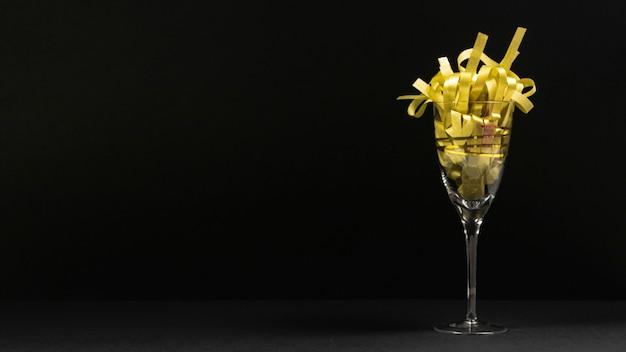 Scena nera con un bicchiere e scintillii