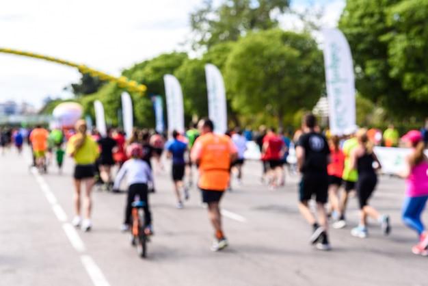 Scena sfocata di corridori di una corsa popolare con bambini e anziani che fanno esercizio di jogging.