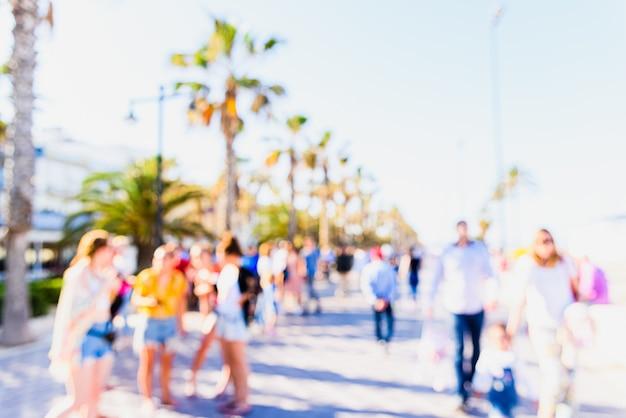 Scena sfocato da utilizzare come muro di una passeggiata con palme e turisti in vacanza.