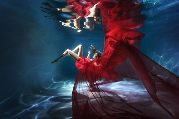 Scena subacquea. una donna, una modella in acqua con un bellissimo vestito nuota come un pesce.