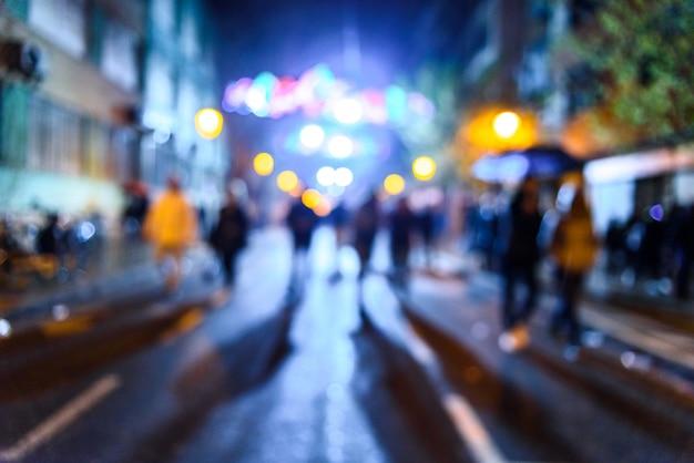 Scena urbana di notte con la gente che cammina sfuocato con fondo colorato.