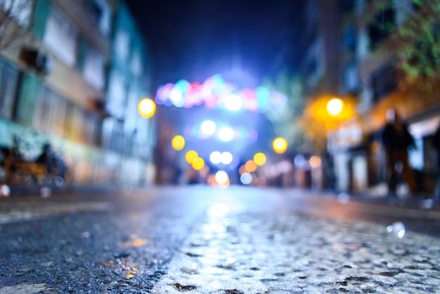 Scena urbana di notte con persone che camminano sfuocato