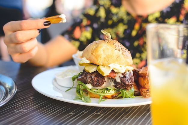 Scena variopinta della signora che mangia un hamburger succoso del manzo di estate