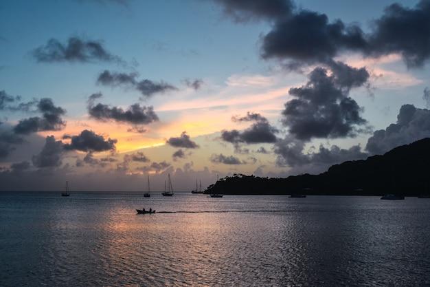 Scenario del tramonto con una silhouette di montagna e barche nel mare