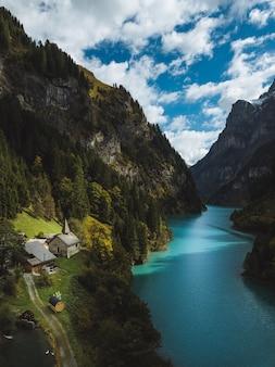 Scenario di un bellissimo fiume tra le montagne e le casette sotto il cielo nuvoloso