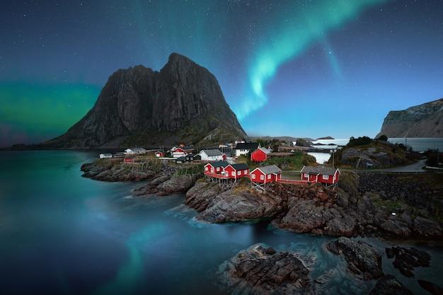 Scenario mozzafiato di aurora boreale su un villaggio sul mare vicino a scogliere rocciose