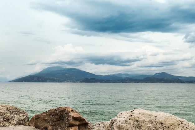 Scenario naturale del lago di garda in italia. paesaggio molto bello, lago pulito di acqua dolce con acqua turchese, montagne all'orizzonte, nuvole nel cielo.