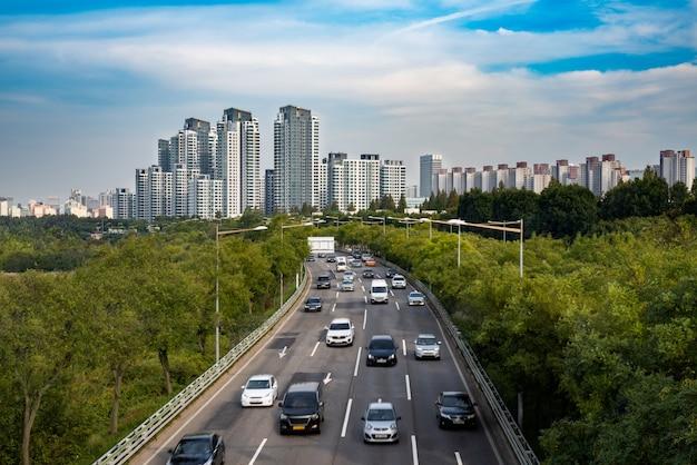 Scenario stradale di auto urbana con edifici e spazi verdi.