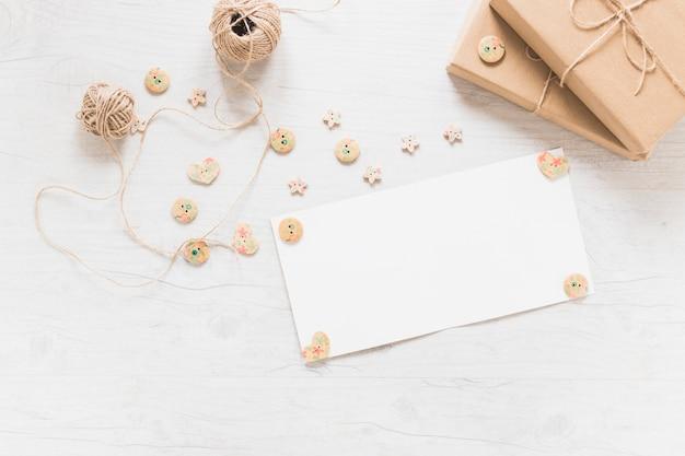 Scheda bianca vuota decorata con bottone in legno con rocchetto e scatole