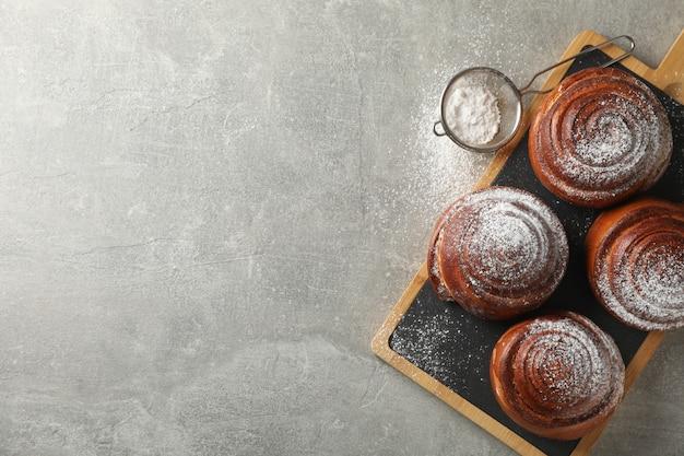 Scheda con rotoli di cannella con zucchero a velo su grigio