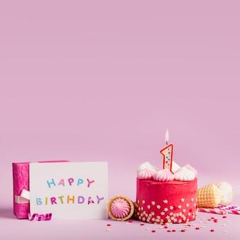 Scheda di buon compleanno vicino al dolce con candele accese e confezione regalo sullo sfondo viola