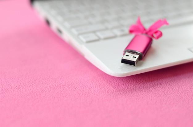Scheda di memoria flash usb brillante rosa con un fiocco rosa