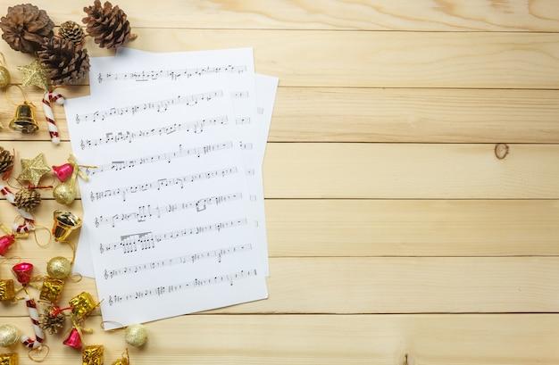 Scheda di nota superiore della carta di nota carta e decorazione di natale su priorità bassa di legno